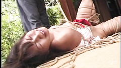 Tied Asian girl lying half naked on the bare ground